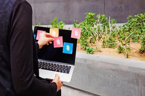 בן אדם מחזיק מחשב בגינה עם מדבקות