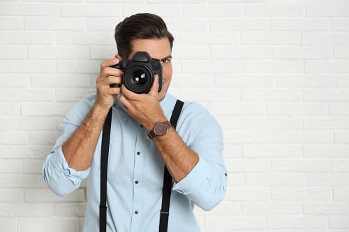 בחור עם חולצה כחולה מחזיק מצלמה